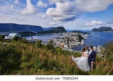 Alesund, Norway - June 11, 2017: Wedding photo session in Alesund, Norway. Two happy people standing on Aksla hill. Alesund city in background