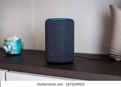 Alexa portable echo speaker device on a wooden shelf. Italy, Torino - February 2020