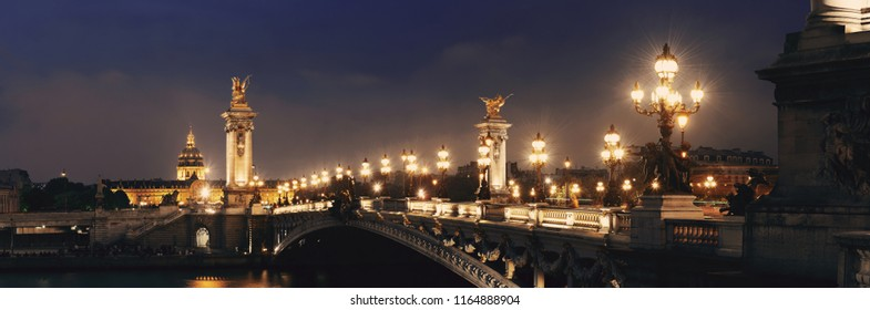 Alexandre III bridge night view panorama with Napoleon's tomb in Paris, France.