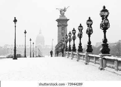 The Alexandre III bridge of Paris under the snow with the Invalides in the background