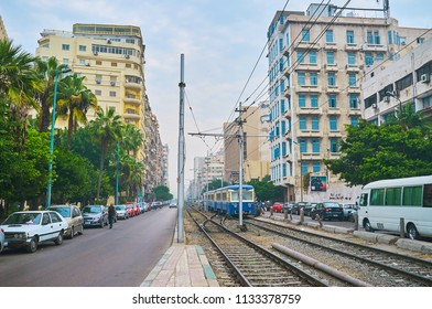 ALEXANDRIA, EGYPT - DECEMBER 18, 2017: The vintage tram of Al Ramlh tramway network rides along Omar Lotfy street with tall residential buildings on both sides, on December 18 in Alexandria.