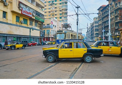 ALEXANDRIA, EGYPT - DECEMBER 18, 2017: The old yellow-black taxi cars ride across the railroad in Mahta Al Raml square, on December 18 in Alexandria.