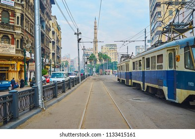 ALEXANDRIA, EGYPT - DECEMBER 18, 2017: Old blue tram rides along historical Mahta Al Raml square with a view on white minaret of Al Qaed Ibrahim Mosque on the distance, on December 18 in Alexandria.