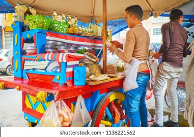 ALEXANDRIA, EGYPT - DECEMBER 18, 2017: The young cooks make popular Egyptian street food - tameya (falafel) in pita with eggs, vegetables and fool (beans), on December 18 in Alexandria.