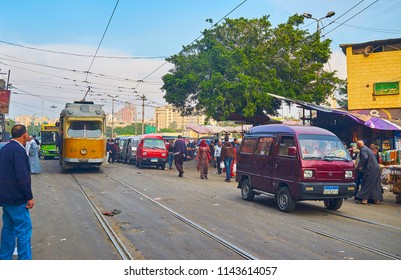 ALEXANDRIA, EGYPT - DECEMBER 18, 2017: The old yellow tram rides along Sharif avenue in market area, this place is always crowded and noisy, on December 18 in Alexandria.