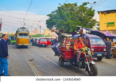 ALEXANDRIA, EGYPT - DECEMBER 18, 2017: The market vendors ride on motorcycle cargo trailer along the tramway in Sharif Avenue with vintage tram on the background, on December 18 in Alexandria.