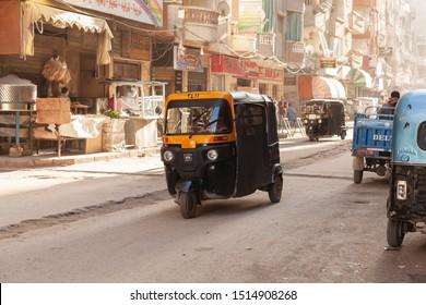 Alexandria, Egypt - December 18, 2018: Street view of Alexandria, auto rickshaw is on the street, ordinary people walk the street
