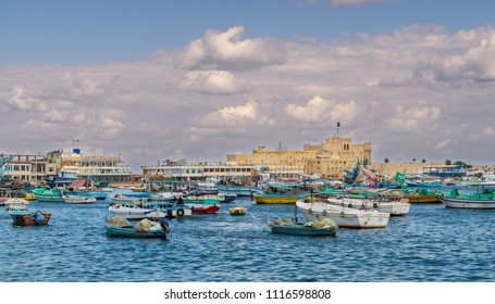 Alexandria, Egypt - December 3 2015: Old east harbor of Alexandria city at the Mediterranean Sea with fishing boats in the foreground and the Citadel of Qaitbay in the background in cloudy winter day