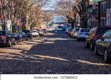 Alexandria, VA / United States - 3/12/19: Cobblestone street lined with parked cars in Alexandria, VA with Potomac River in background