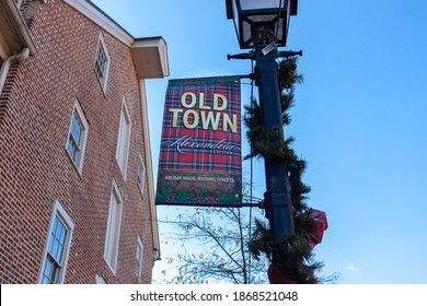 Alexandria, VA, USA 11-28-2020:  A banner on a lamp post promoting popular tourist spot Old Town region of historic Alexandria. There are ribbons wreaths on the post due to upcoming holiday season.