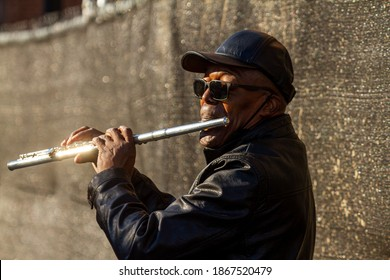Alexandria, VA, USA 11-28-2020: Close up, isolated image of an African American male street musician playing flute in the historic district of Alexandria. He wears sunglasses and black outfit.