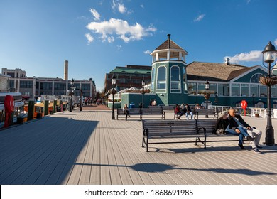 Alexandria, VA, USA 11-28-2020: A sunny day on the waterfront of the old town district of Alexandria with people sitting on benches on the pier in front of the lighthouse. There are docked vessels.