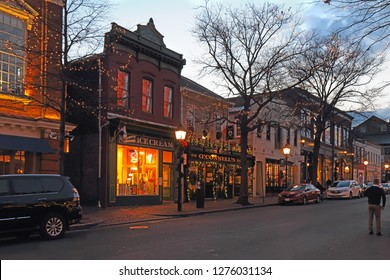 ALEXANDRIA, VIRGINIA - DECEMBER 7 2017: Businesses along King Street, one of the main thoroughfares running towards the Potomac River in Old Town Alexandria, with holiday decorations at night.