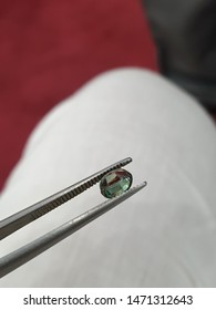 an Alexandrite being held with tweezers by a gemmologist for inspection.