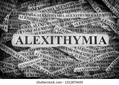 Alexithymia. Torn pieces of paper with the words Alexithymia. Concept image. Black and White. Close up.