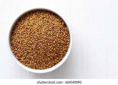 Alfalfa seeds in white ceramic bowl isolated on painted white wood from above.