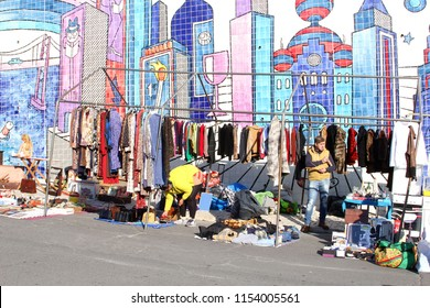 ALFAMA, LISBON, PORTUGAL - January 21, 2017. Sales man is selling used clothing and secondhand stuff at outdoor flea market Feira da Ladra and walls of Portuguese tile patterns at the background.