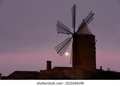 Algaida, Mallorca, Spain - 2019: Moonset behind the blades of a mill