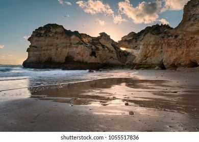 Algarve beach at sunset with a sun beam shooting through an opening in the rocks