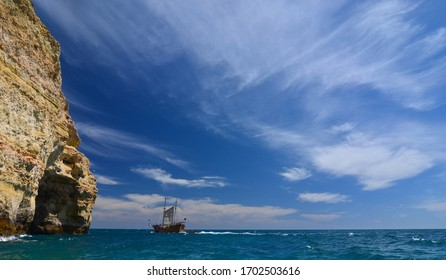Algarve coast, ship on the sea at the rock cliff