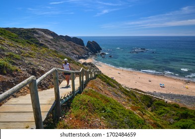 Algarve coast, stairway on the beach, woman on the stairs