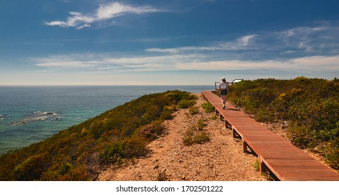 Algarve coast and walking woman on the edge of cliff