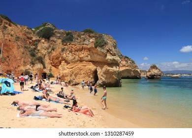 ALGARVE, PORTUGAL - MAY 29, 2018: Tourists visit Camilo Beach in Algarve region, Portugal. Coastal region of Algarve attracts more than 17 million tourists annually.