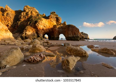 Algarve sea arches at sunset with a person in the  distance