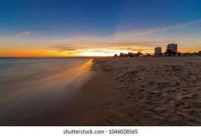 Algarve sunset on the beach at Alvor near Portimao, in the background Lagos