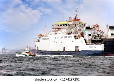 ALGECIRAS, SPAIN – APRIL 23: Ferry AMMAN leaving Algeciras harbour helped by the pilot cutter; on august 23, 2018 in Spain.