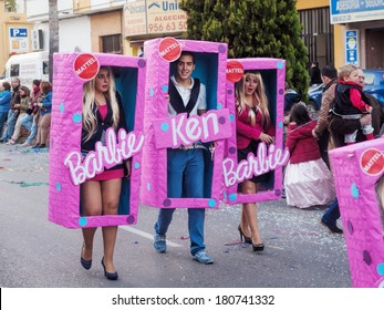 ALGECIRAS, SPAIN - MARCH 08, 2014: 2 women  a man disguised as Barbies and Ken in a boxes during the parade of the carnival in the street  in Algeciras, Cadiz, Andalusia