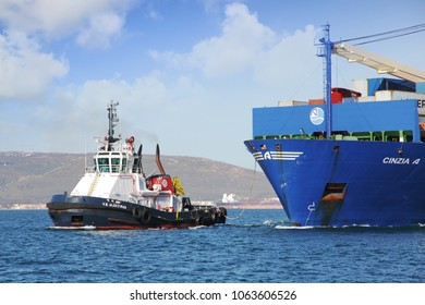 ALGECIRAS, SPAIN – MARCH 25. Power tug working next to the container ship CINCIA A approaching to the port of Algeciras, on march 25, 2018 in Cadiz.