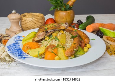 Algerian food: couscous, tagine, barbecued whole lamb, algerian rechta, chicken beef and lamb. Served on a plate with decoration and vegetables.