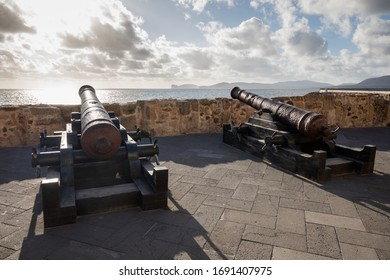Alghero, Italy - 26 September 2019: Two canons at sun down at fortress of Alghero, Italy