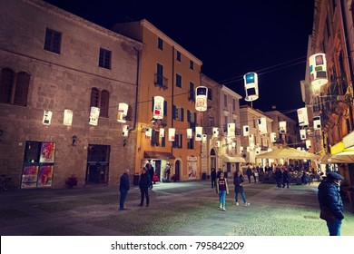 Alghero, Italy - January 07, 2018: People in Piazza Civica at night