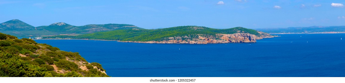 Alghero, Italy - Panoramic view of the Gulf of Alghero with cliffs of Punta del Giglio and city of Alghero in background