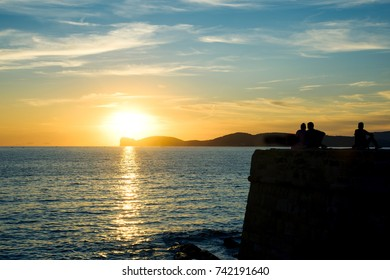 ALGHERO, ITALY -SEPTEMBER 17, 2017: People watching the sunset at the Mediterranean sea on the walls of the Old Town of Alghero, Sardinia, Italy