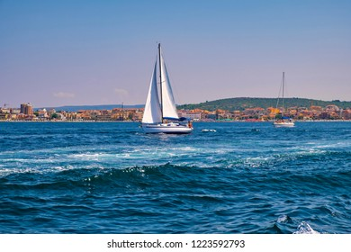 Alghero, Sardegna / Italy - 2018/08/09: Panoramic view of the Gulf of Alghero with sailboats and the historic city of Alghero in background