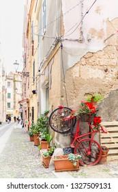 Alghero, Sardinia island, Italy - December 28, 2019: Colorful red bike with flowers in the street of Alghero, Sardinia island in Italy