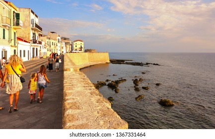 Alghero, Sardinia Italy 01.08.2017. Family walks in Alghero old town quarter with historic defense walls and the coastline of Gulf of Alghero at Mediterranean Sea