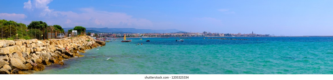 Alghero, Sardinia / Italy - 2018/08/08: Panoramic view of the Gulf of Alghero with historic quarter and Alghero old town in background