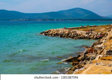 Alghero, Sardinia / Italy - 2018/08/08: Summer skyline view of the rocky Alghero coast and beach at the Gulf of Alghero at Mediterranean Sea with the Old Town historic quarter in background