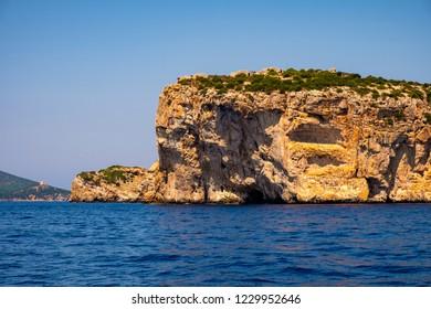 Alghero, Sardinia / Italy - 2018/08/09: Faro di Capo Caccia lighthouse at the limestone cliffs of the Capo Caccia cape at the Gulf of Alghero