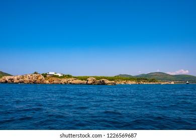 Alghero, Sardinia / Italy - 2018/08/09: Limestone cliffs of the Capo Caccia cape at the Gulf of Alghero