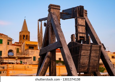 Alghero, Sardinia / Italy - 2018/08/10: Summer sunset view of the Alghero old town quarter with historic defense walls, fortifications and catapult construction