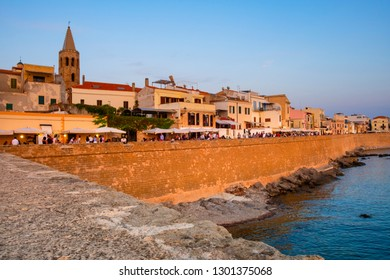 Alghero, Sardinia / Italy - 2018/08/10: Summer sunset view of the Alghero old town quarter with historic defense walls and the coastline of Gulf of Alghero at Mediterranean Sea