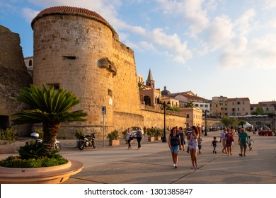 Alghero, Sardinia / Italy - 2018/08/10: Summer sunset view of the Alghero old town quarter with historic defense walls and fortifications