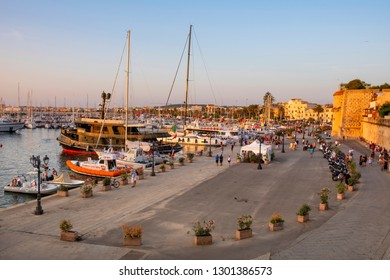 Alghero, Sardinia / Italy - 2018/08/10: Summer view of the Alghero Marina yacht port at the Gulf of Alghero with historic defence walls and the Banchina Dogana boulevard