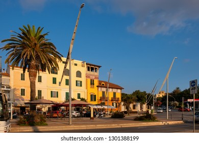 Alghero, Sardinia / Italy - 2018/08/10: Summer view of the Alghero old town quarter at the Gulf of Alghero with historic defense walls and the Banchina Dogana boulevard