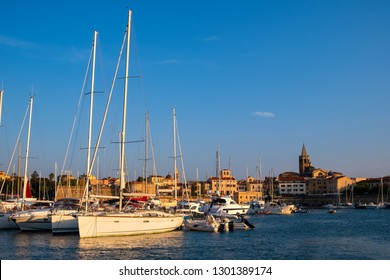 Alghero, Sardinia / Italy - 2018/08/10: Summer view of the Alghero Marina yacht port at the Gulf of Alghero at Mediterranean Sea with the Old Town quarter with historic defense walls